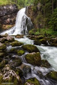 ein Wasserfall mit Bach im vordergrund, umrandet von Felsen und Wald
