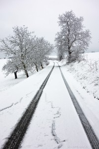 Verschneite Straße mit einer ersten Fahrspur