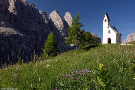 Weiße Kapelle vor strahlend blauen Himmel, umgeben von felsigen Bergflanken