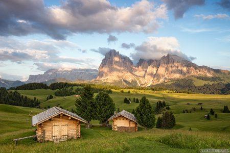 zwei Berghütten auf einer grünen Wiese vor Felsgipfeln